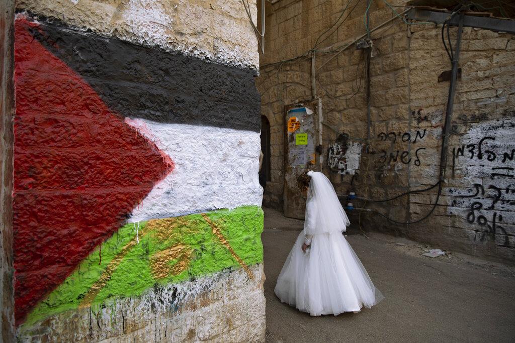 Gerusalemme. Una sposa ebrea passa accanto a un muro con una bandiera palestinese