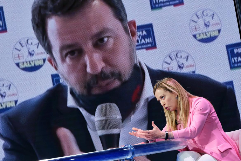 Giorgia Meloni e sullo sfondo Matteo Salvini