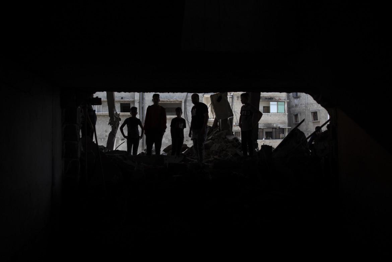 Gaza City, palestinesi ieri tra le macerie delle loro case distrutte dai bombardamenti aerei israeliani