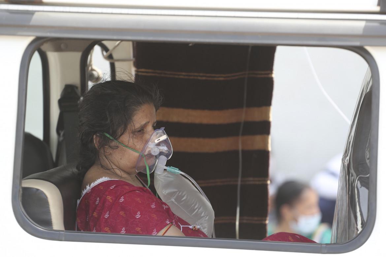 Una donna indiana in attesa del ricovero in un ospedale Covid di Ahmedabad