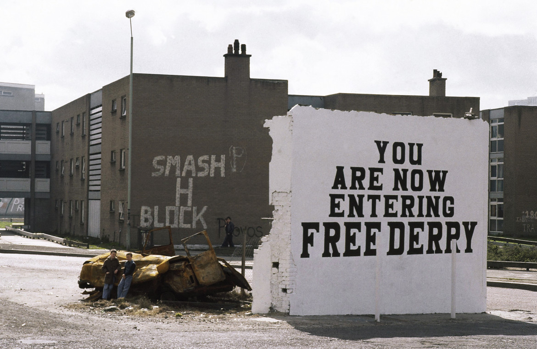 Una foto del 5 maggio 198: protesta a Belfast dopo la morte di Bobby Sands; in basso il murale a lui dedicato sulla sede dello Sinn Féin e il Memoriale con la forma del blocco H della prigione Maze