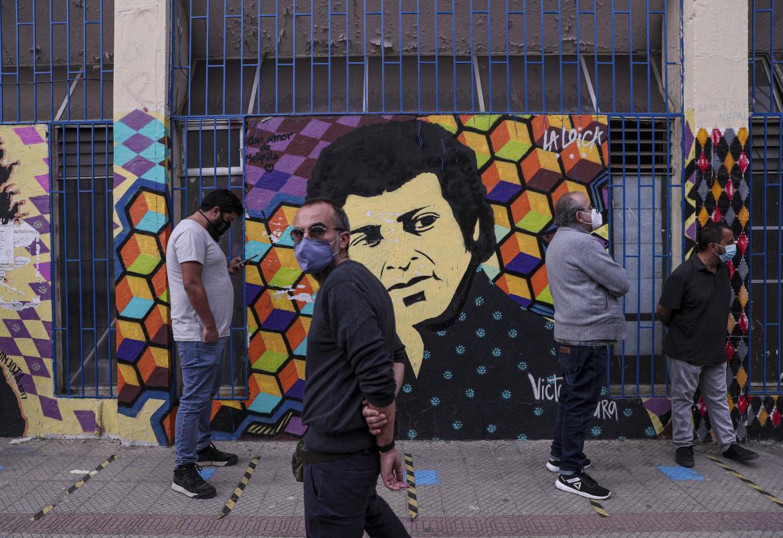 In fila per votare a Santiago di fronte a un murale dedicato a Victor Jara, indimenticato cantautore comunista ucciso dal regime di Pinochet