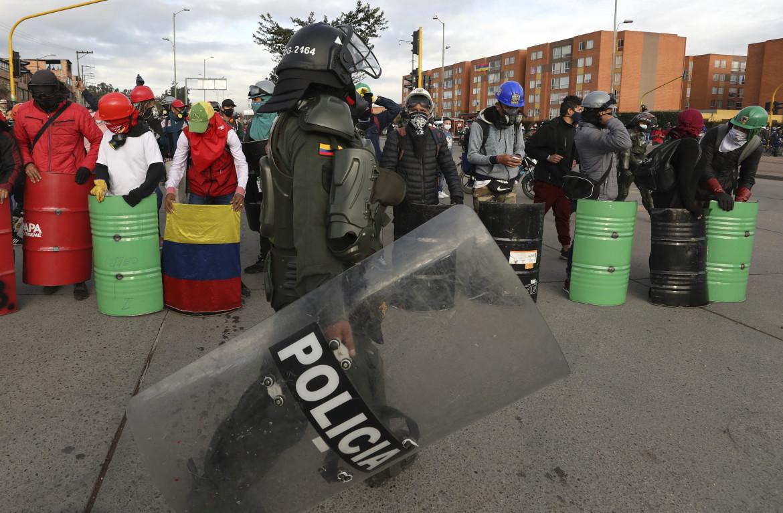 18 maggio, manifestanti con scudi protettivi autocostruiti durante il blocco di un terminal dei bus a Bogotà