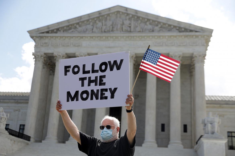 Un uomo con il cartello «Follow the Money» di fronte alla Corte Suprema Usa nel 2020 durante le indagini sui patrimoni di Trump foto Getty