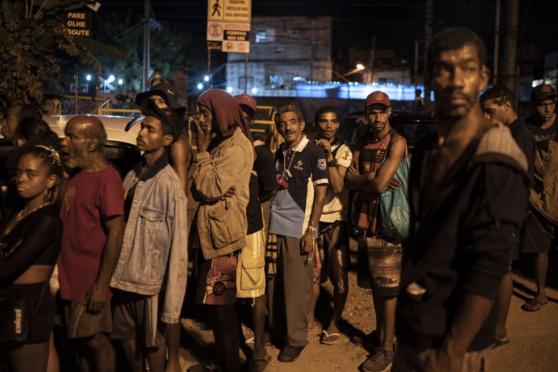 La fila per i pasti caldi distribuiti dall'Instituto Anjos da Liberdade nel quartiere in piena pandemia