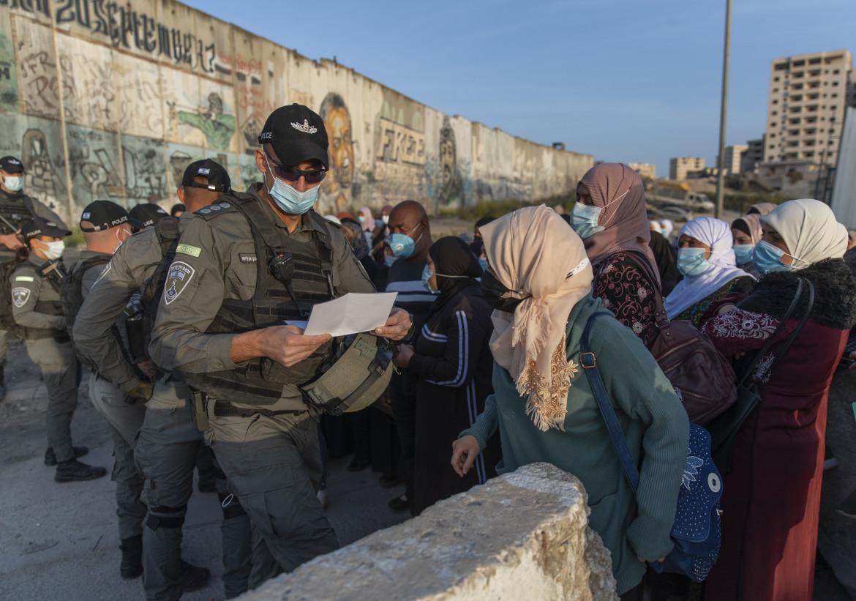 Cisgiordania. Donne palestinesi esibiscono il certificato vaccinale per poter attraversare il checkpoint di Qalandia