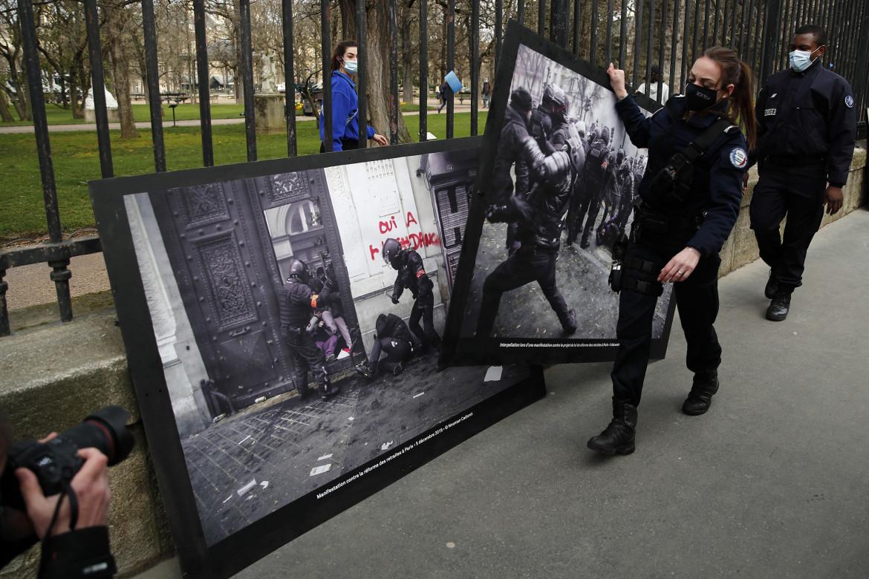 Agenti rimuovono le foto della violenza della polizia appese dagli attivisti di Attac e Greenpeace