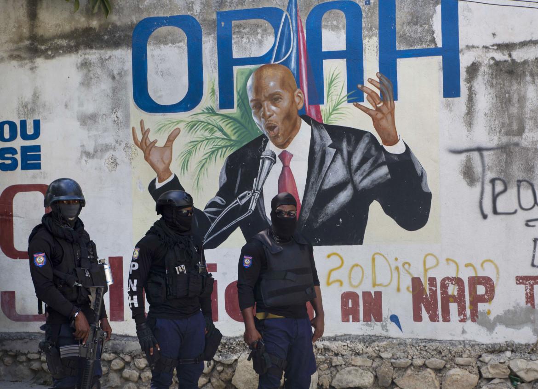 La polizia haitiana ieri davanti a un murale dedicato a Jovenal Moïse non lontano dalla sua abitazione