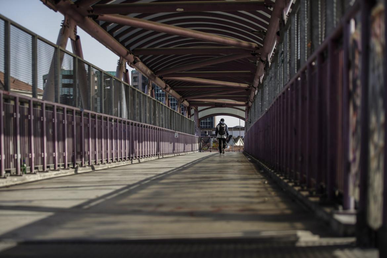 Un uomo cammina sul ponte accanto al Cpr di via Corelli