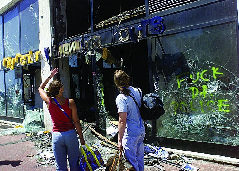 Turisti osservano alcune vetrine rotte in seguito agli scontri di Genova 2001