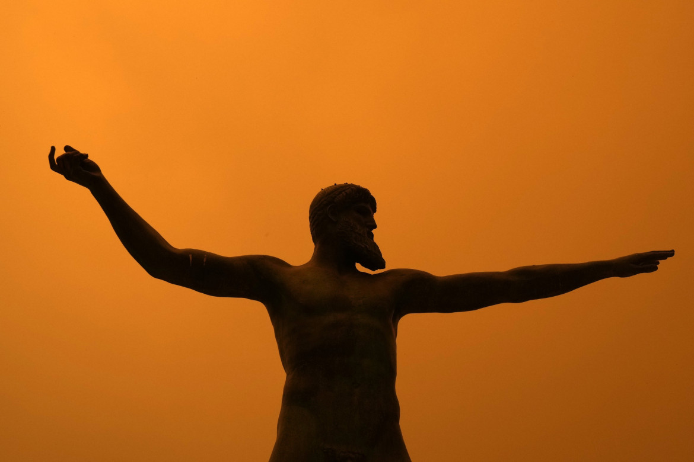 La statua di Poseidone sullo sfondo degli incendi a Evia, Grecia