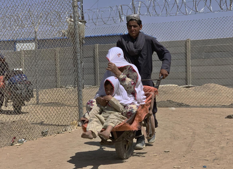 Un uomo spinge una carriola con sopra una donna e suo figlio mentre entrano in Pakistan dall'Afghanistan