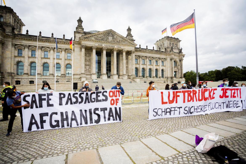 Berlino, manifestazione davanti al Reichstag per chiedere l'evacuazione di quante più persone dall'Afghanistan; in basso Frank-Walter Steinmeier