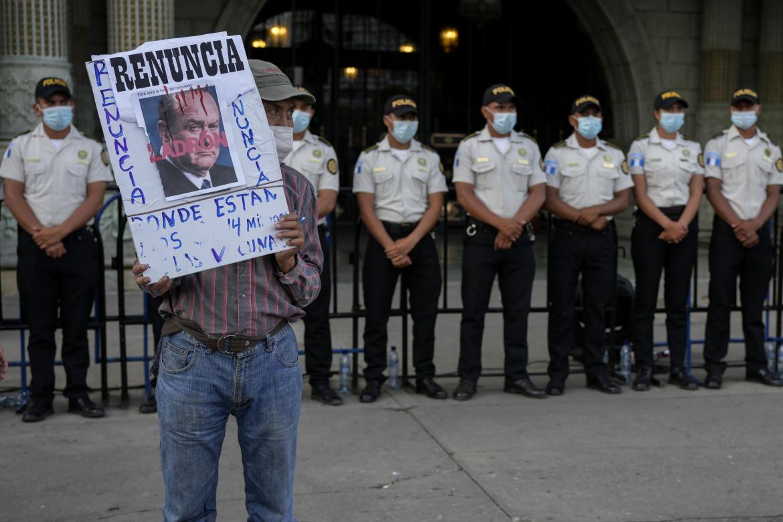 Un manifestante con una foto di Giammattei fuori dal Palazzo Nazionale a Guatemala City