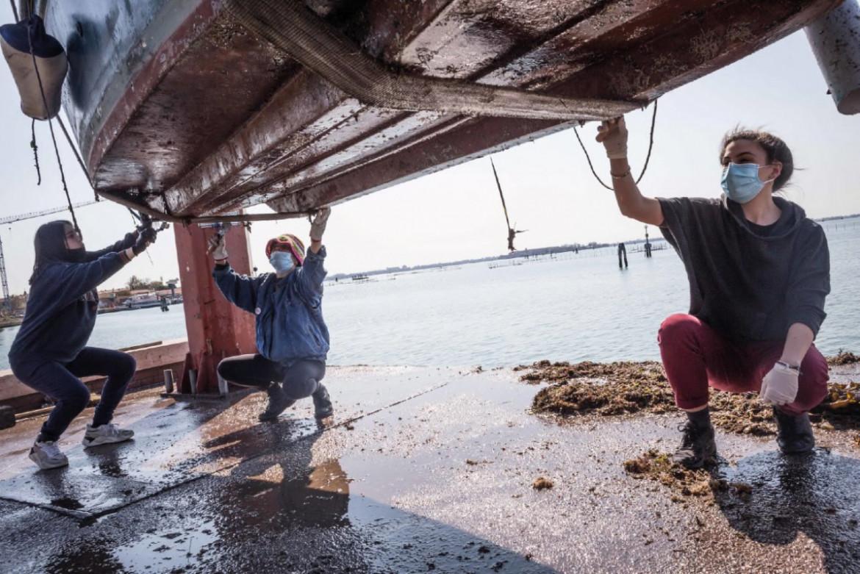 Daniela, Sofia e Clare, studentesse a Venezia legate a «Fie a Manetta» mentre puliscono lo scafo della barca di Marta Sottoriva
