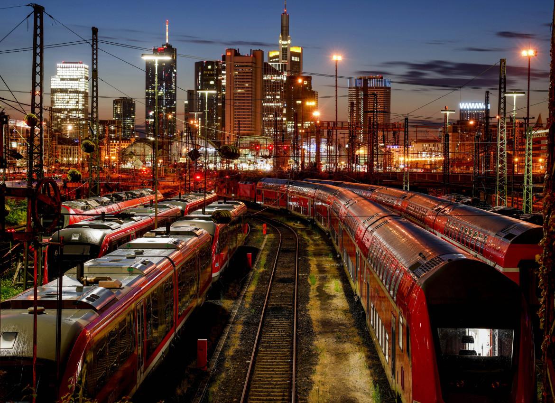 Treni fermi nel deposito della stazione di Francoforte, in basso passeggeri in attesa