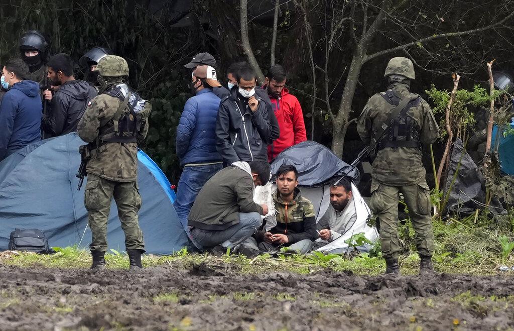 Migranti sorvegliati dalla polizia al confine polacco