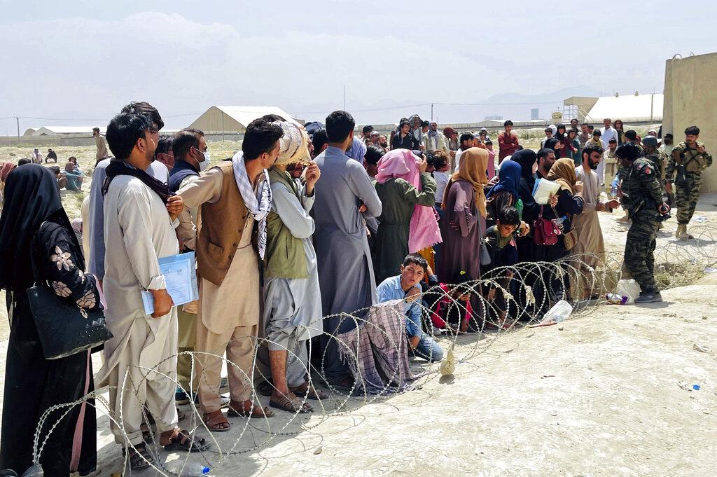 Persone fuori dall'aeroporto di Kabul lo scorso agosto