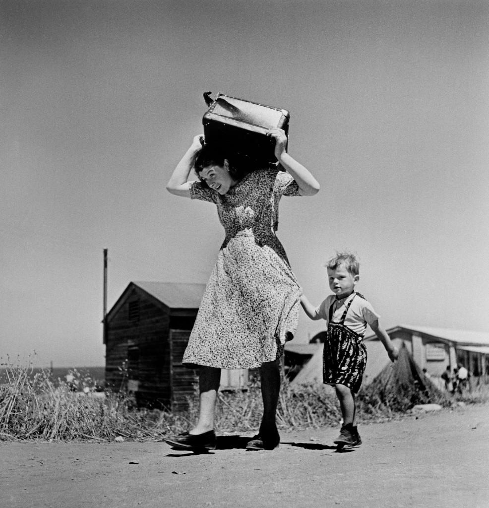 Robert Capa, Donna porta i suoi bagagli accompagnata  da un bambino, Haifa, Israele, 1949-1950,  foto presa da: Robert Capa, a cura di André Holzherr, Silvana Editoriale, 2012
