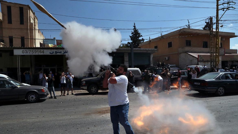 Un sostenitore di Hezbollah spara un razzo anticarro per festeggiare l'arrivo delle autocisterne cariche di benzina e gasolio