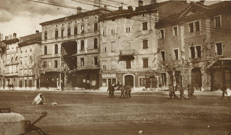Una foto dell'agosto 1916 mostra la facciata di Palazzo Paternolli squarciata da un proiettile, sotto l'edificio in ristrutturazione