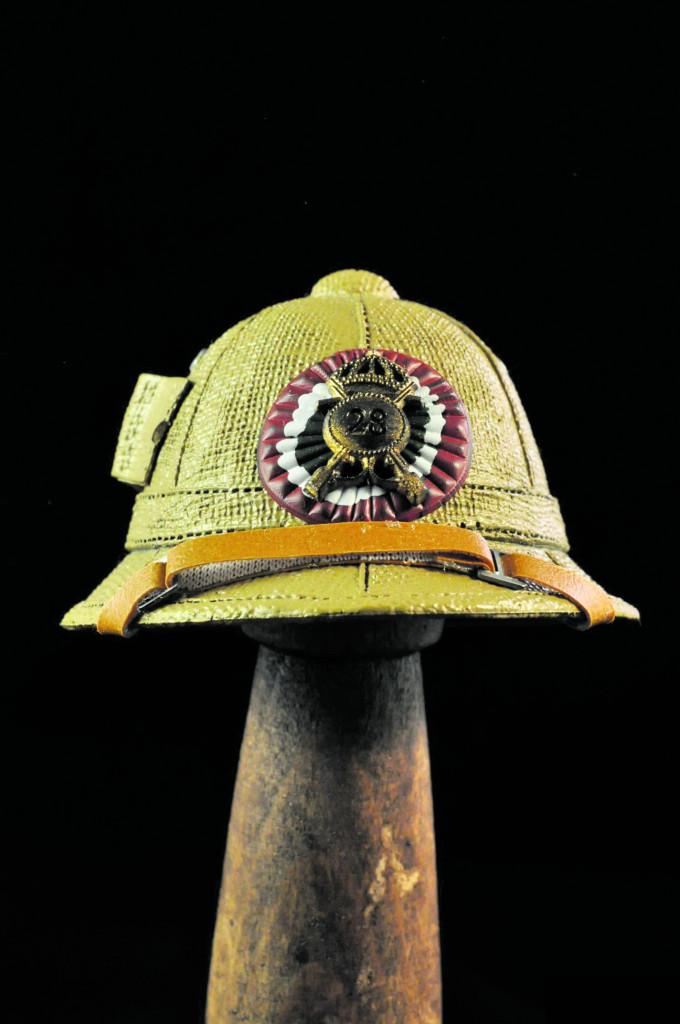 Un casco delle truppe coloniali della Seconda guerra mondiale. In alto e a destra, immagini  della propaganda fascista sulle colonie