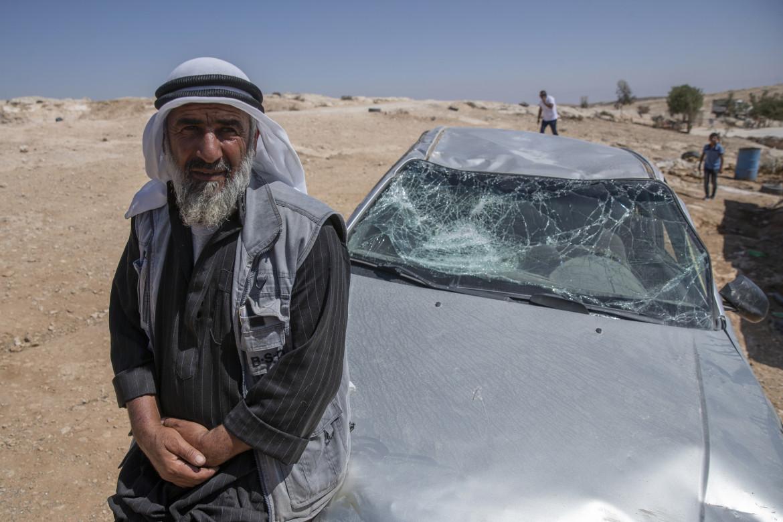 Un abitante di Mufaghara (Hebron) accanto alla sua automobile distrutta dai coloni israeliani